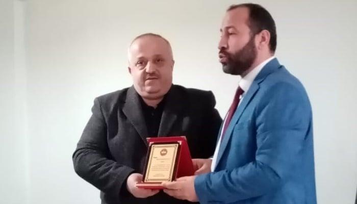 Diyanet Sen Çaykara Temsilcisi Ziya Çamurşen, Müftü Abdurrahman Koç'a plaketini takdim ederken